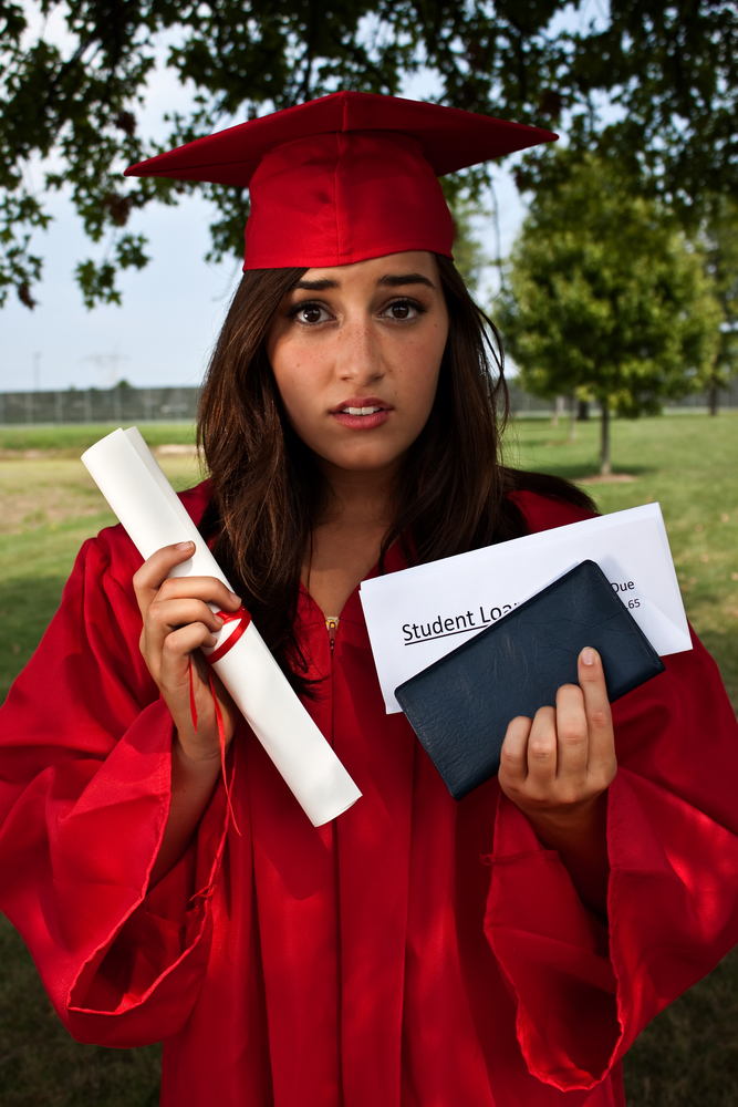 Graduate holding diploma, checkbook and student loan bill. This is a conceptual image about student loans and debt.